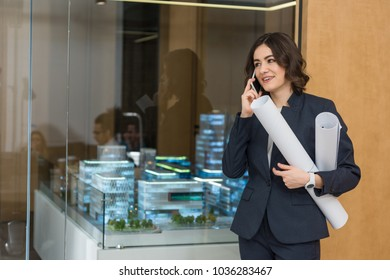 beautiful young architect with rolled building plans talking by phone