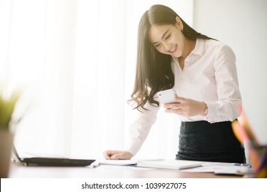 Beautiful young Asia woman working with smart phone in office
