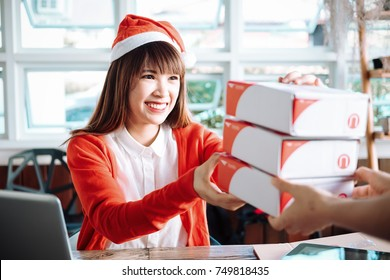 Beautiful young asian business owner working with computer and tabet smiling while standing in workshop.Responding on business e-mail,Delivery of product customer orders.