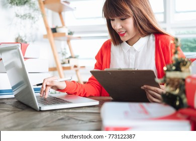 Beautiful young asian business owner working with computer and tabet smiling while standing in workshop.Responding on business e-mail,writing the order of product customer orders.