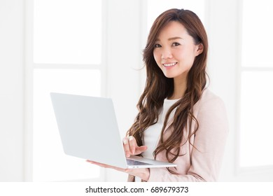 Beautiful young asian businesswoman using laptop