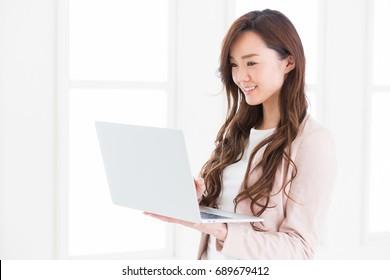 Beautiful young asian businesswoman using laptop