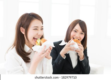 Beautiful young asian businesswomen who eats a hamburger