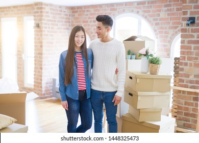 Beautiful young asian couple looking happy and smiling excited moving to a new home