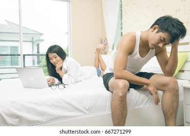 Beautiful young asian couple using laptop and watching movies in bed or shopping online on the bed.Boy friend boring her.