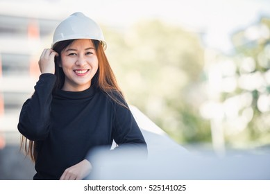 Beautiful young Asian engineer or technician woman smiling, industry or logistic concept, with copy space