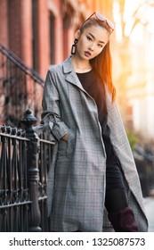 Beautiful young Asian fashion model woman walking on city street wearing jacket and sunglasses