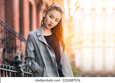 Beautiful young Asian fashion model woman walking out from home in big city at sunny day