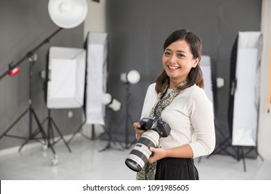 beautiful young asian female photographer standing in studio