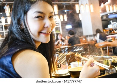 Beautiful young asian girl eating shabu shabu sukiyaki in japanese restaurant