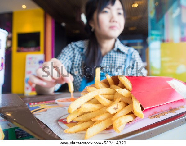 Beautiful young asian girl eating french fries in mosern restuarant