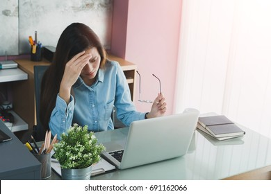Beautiful young Asian girl feeling headache and stress in office space background.Concept of Healthcare and Office syndrome.Vintage tone