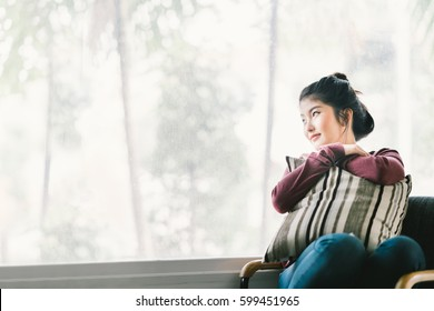 Beautiful young Asian girl relaxing at home, sitting alone by window, looking at copy space. Concept of lonely woman, thinking, or missing someone