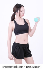 Beautiful young asian girl in sportwear  holding two blue dumbbells on white background. Studio shot, being fit and healthy sport concept. Healthy lifestyle.
