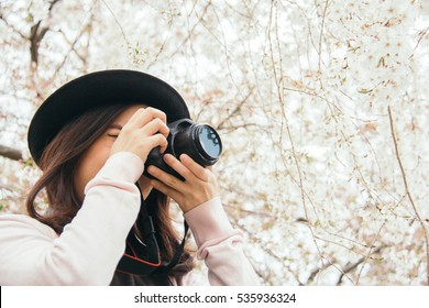 Beautiful young asian girl taking a picture in blooming sakura garden