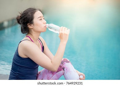 Beautiful young Asian happy woman drinking water after do yoga at swimming pool, outdoor exercise and healthy lifestyle concepts