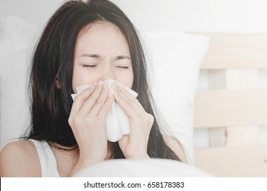 Beautiful young asian having common cold, wiping noses  lying on bed