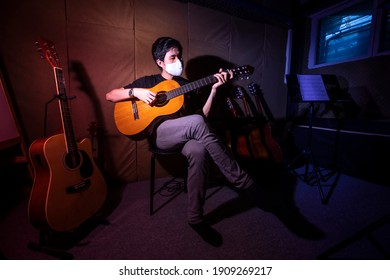 Beautiful young asian man waering face mask and play on guitar. Boy sitting in studio music recording room with acoustic guitar.