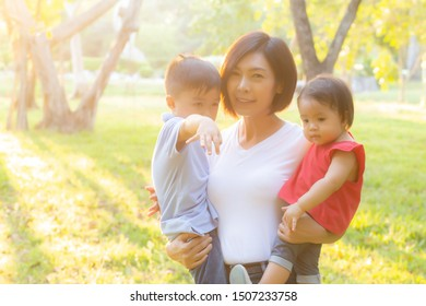 Beautiful young asian mother carrying little boy and girl in the park, asia woman happy having son and daughter and hug kid, mom love and embracing child together, mother day and family concept.