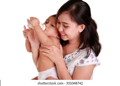 Beautiful young Asian mother giving a bottle of milk to her cute baby daughter, isolated on white background