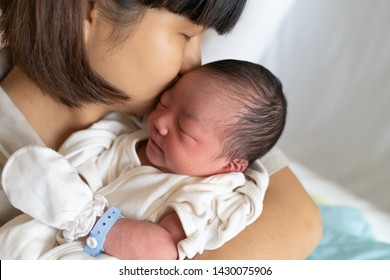 Beautiful young asian mother kissing her newborn baby in mom arms at hospital. Healthcare and medical love lifestyle mother's day concept.  Close up portrait of mother and new born baby.