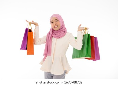 A beautiful young Asian Muslim woman in hijab is holding lot of colorful paper shopping bags with a white background