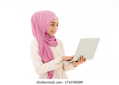 A beautiful young Asian Muslim woman in hijab is using a laptop with a white background