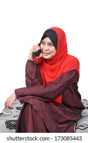 Beautiful young Asian muslim woman happy talking on mobile phone isolated on white background