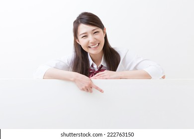 Beautiful young asian school girl holding blank white board