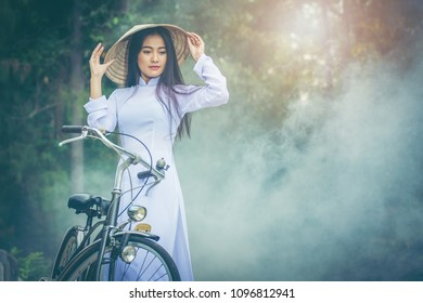 Beautiful young Asian teen with long hair wearing a costume of Viet Nam (Ao dai) she is currently towed a bicycle and holding a hat by verdant gardens background amid the smog and Sun morning.
