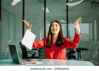 Beautiful young asian thai businesswoman in red shirt throwing paper up in the air in office room.