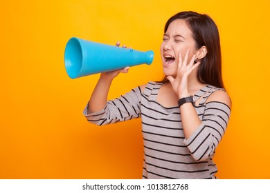 Beautiful young Asian woman announce with megaphone on yellow background