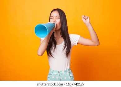 Beautiful young Asian woman announce with megaphone on bright yellow background