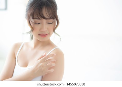 Beautiful young asian woman applying cream and treatment skin care touch on shoulder, asia girl with lotion spa moisturizing for health and wellness body part, lifestyle and beauty cosmetic concept.
