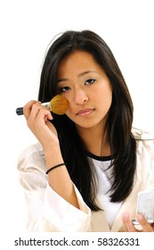 Beautiful young Asian woman applying blush with brush in robe