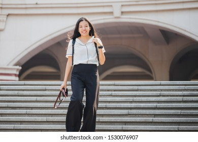 Beautiful young asian woman with backpack holding camera while going down stairs.Concept of peple travel in urban city.