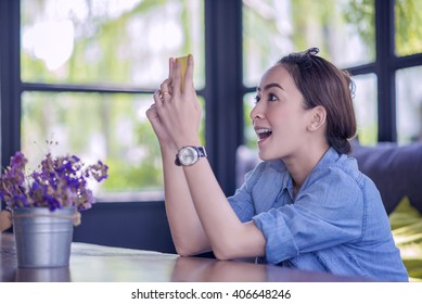 Beautiful young Asian woman being looking at phone seeing surprised message news or photos there with disgusting emotion on her face