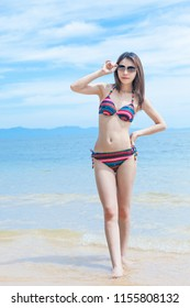 Beautiful Young Asian woman in bikini relaxing on the beach,Travel summer vacation concept.