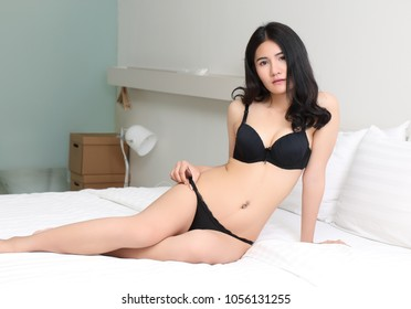 beautiful young asian woman in black bikini at bed room