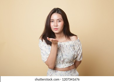 Beautiful young Asian woman blow a kiss on beige background