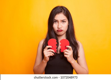 Beautiful young Asian woman with broken heart on yellow background