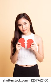 Beautiful young Asian woman with broken heart   on beige background