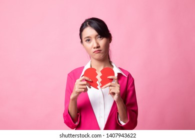 Beautiful young Asian woman with broken heart on pink background - Shutterstock ID 1407943622
