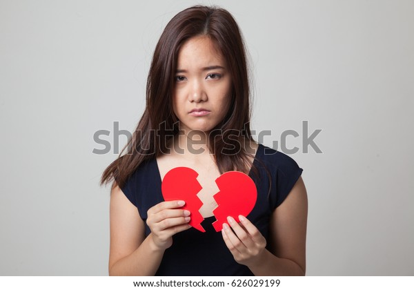 Beautiful young Asian woman with broken heart on gray background