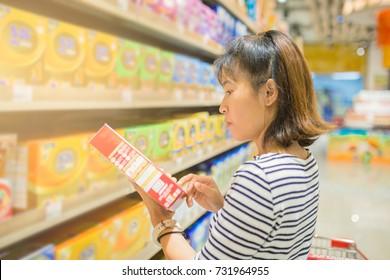 Beautiful young Asian woman choosing milk powder in a supermarket