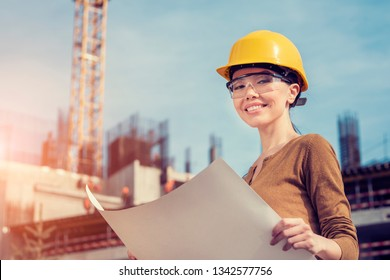 a beautiful young Asian woman civil engineer or architect is reviewing engineering plans in front of a construction site