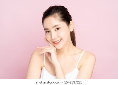 Beautiful Young Asian woman with clean fresh white skin touching her own face softly in beauty pose. Girl touching with fingers in pink background. Facial treatment, cosmetology, spa, make up concept.