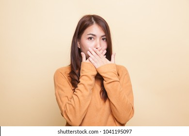 Beautiful young Asian woman close her mouth on beige background