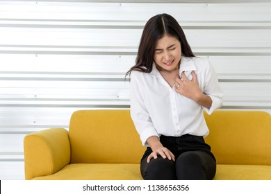 Beautiful Young Asian woman clutching his chest from acute pain or suffering Sharp Strong Pain In Chest while sitting on sofa,woman disease symptoms. Heart attack symptom,Healthcare,medical concept.