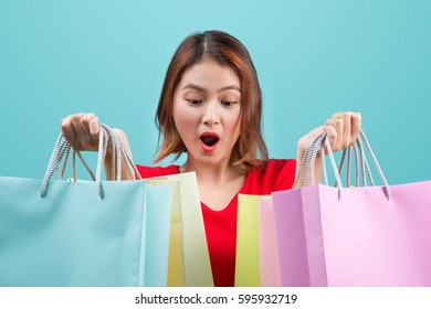 Beautiful young asian woman with colored shopping bags over blue background